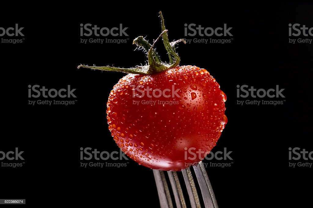 Tomato single with drops isolated on black stock photo