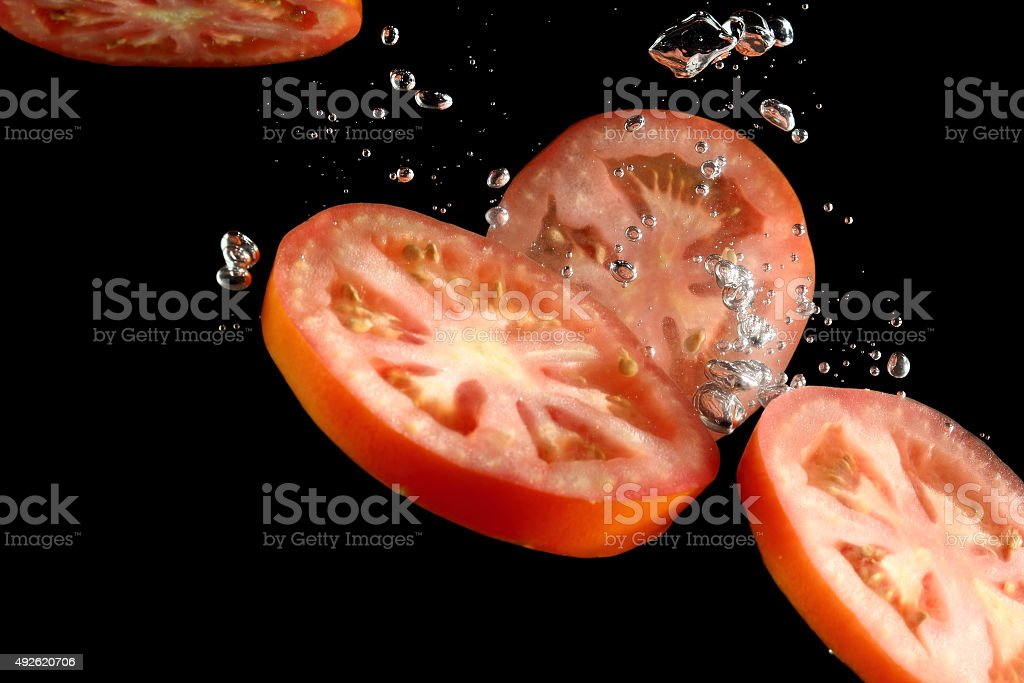 Tomato slices falling into water at black background stock photo