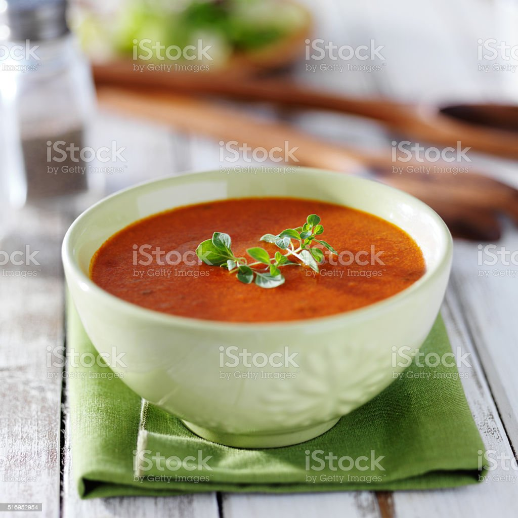 tomato soup in green bowl stock photo