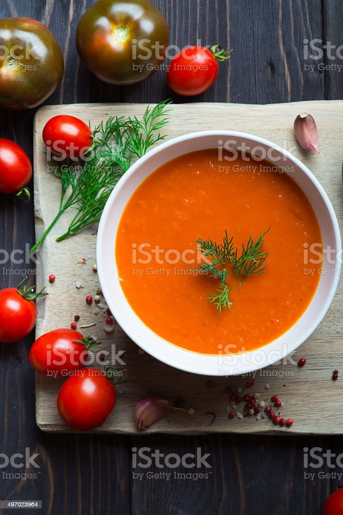 Tomato soup on a wooden table stock photo