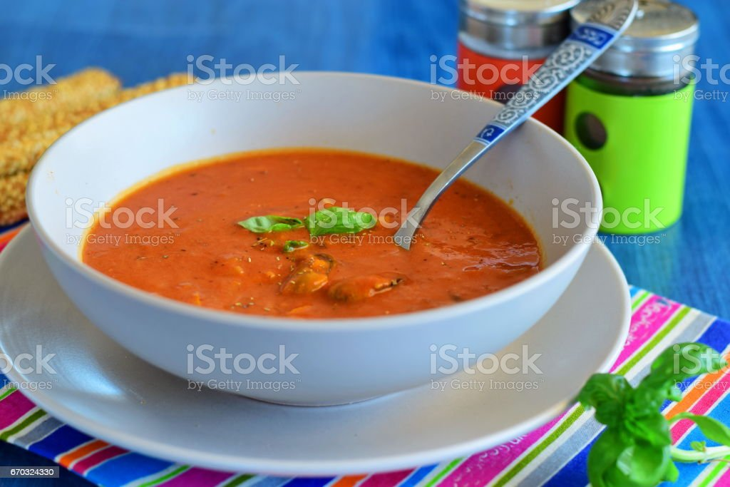 Tomato soup with mussels in a blue bowl on a blue background with bread sticks. Healthy eating concept. stock photo