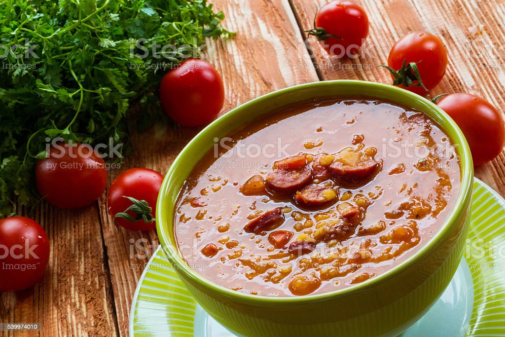 Tomato soup with smoked sausage, tomatoes and lentil stock photo