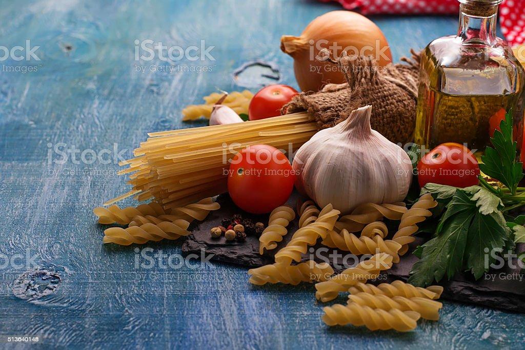 Tomato, uncooked pasta, garlic, parsley stock photo