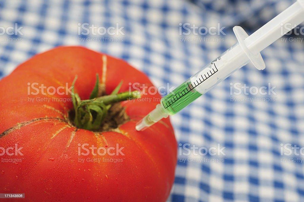 Tomato with syringe stock photo