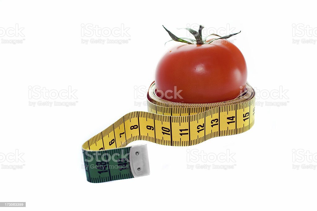 Tomatoe in a measuring tape royalty-free stock photo