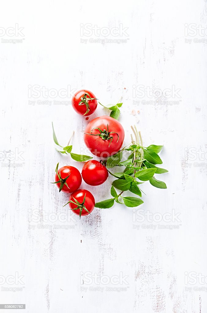 Tomatoes and Basil on a Wooden Background stock photo