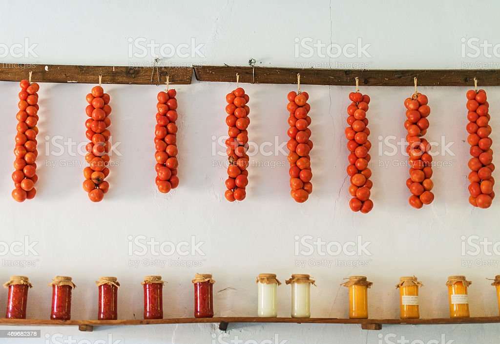 Tomatoes and canned food on wooden shelf. stock photo
