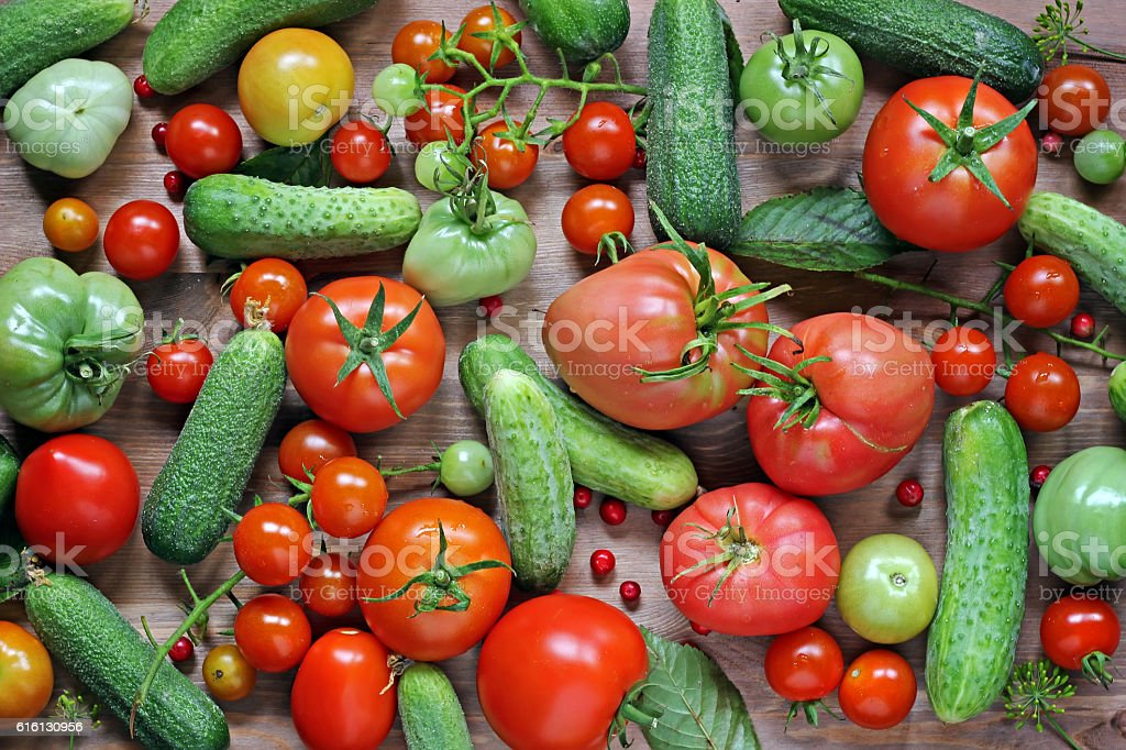 Tomatoes and cucumbers on a table, the top view. stock photo