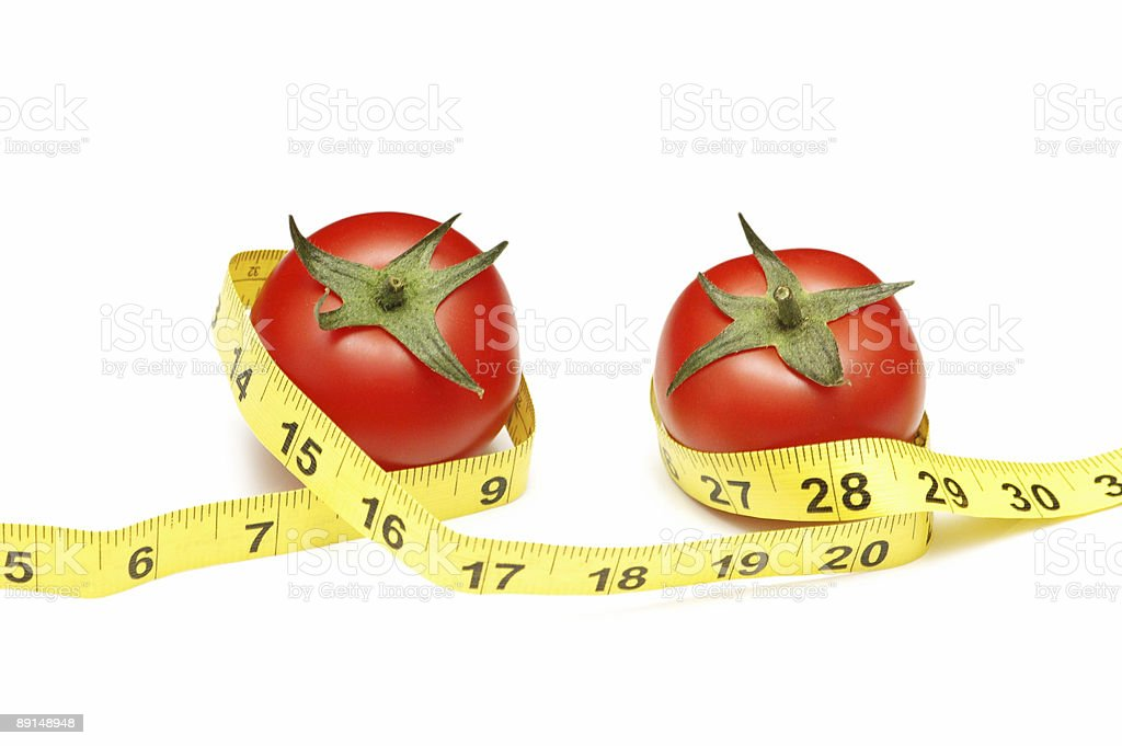 Tomatoes and measuring tape illustrating dieting concept royalty-free stock photo