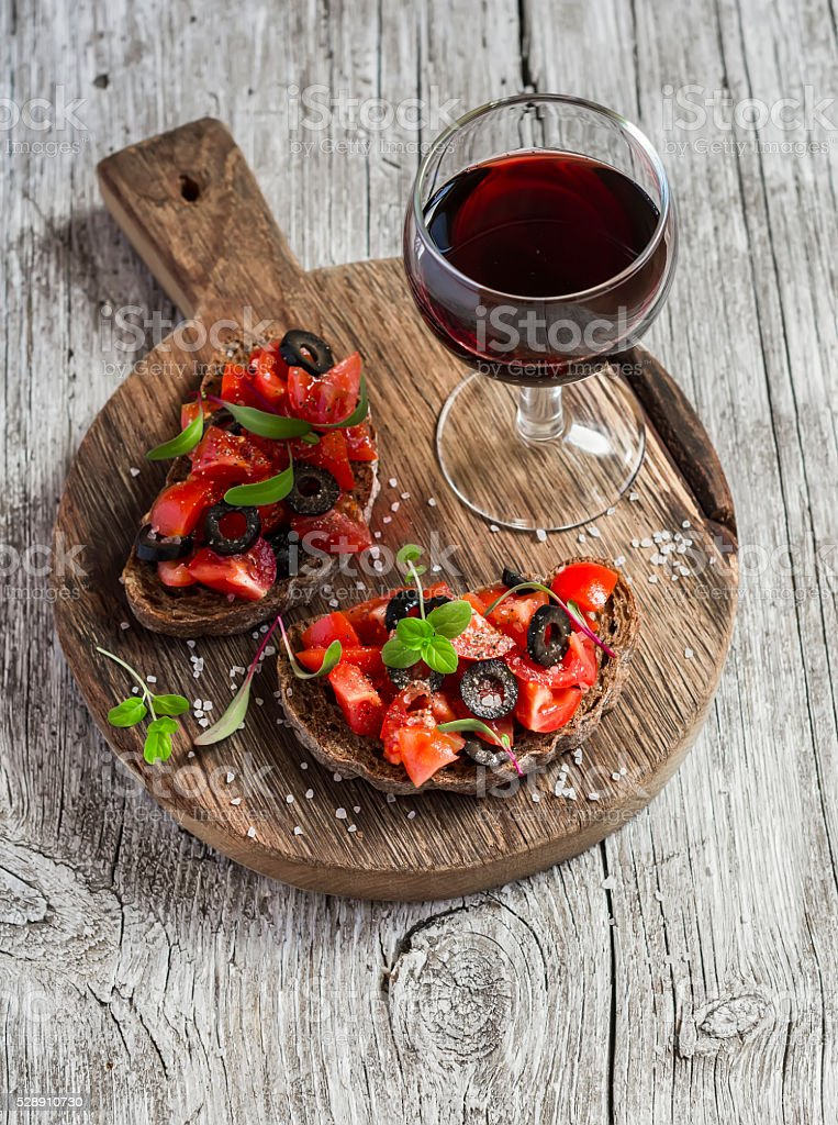 Tomatoes and olives bruschetta and a glass of red wine stock photo