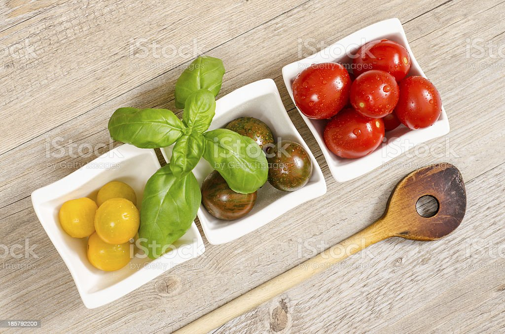 Tomatoes, basil and wooden spoon royalty-free stock photo