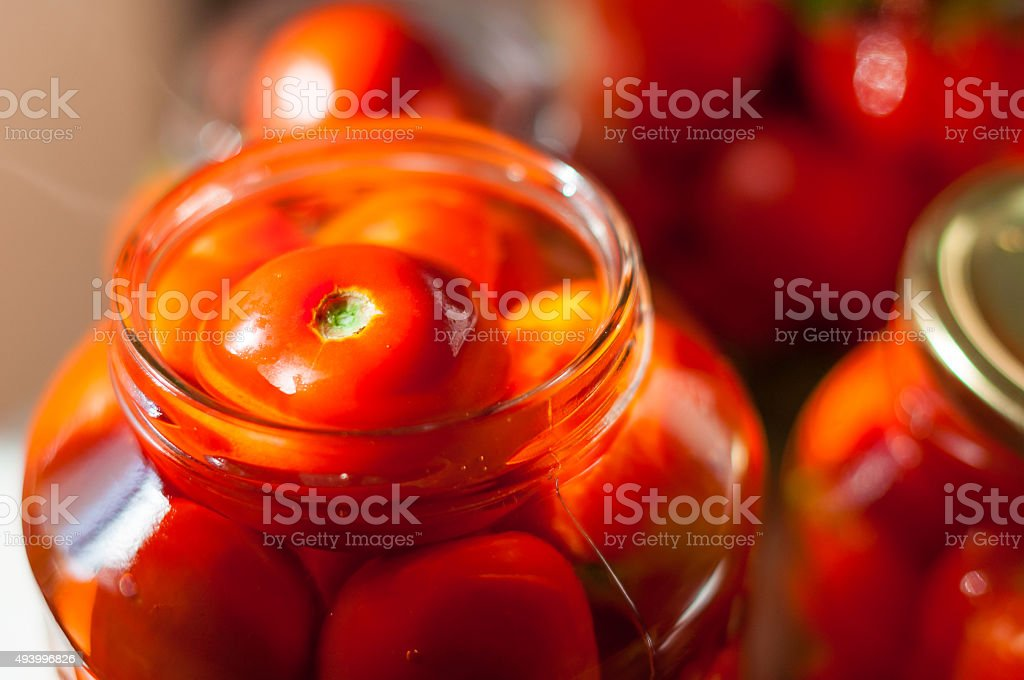 Tomatoes being swamped boiled water in process of canning. Canned stock photo