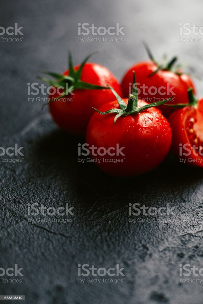 Tomatoes, covered with drops of water on a dark stock photo