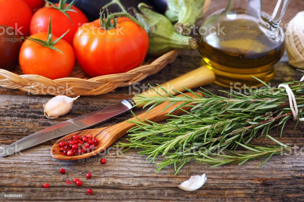 Tomatoes, eggplant, red peppercorns, olive oil and bunch of rosemary stock photo