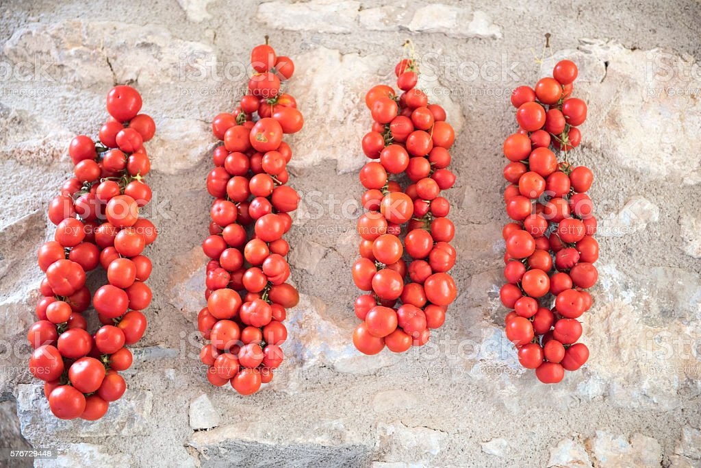 Tomatoes hanging outside on stone wall to be sun-dried stock photo