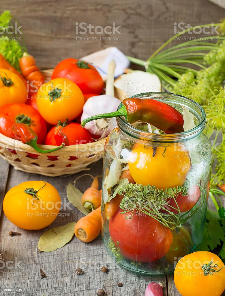 Tomatoes, herbs, garlic, glass jar - set for home canning. stock photo