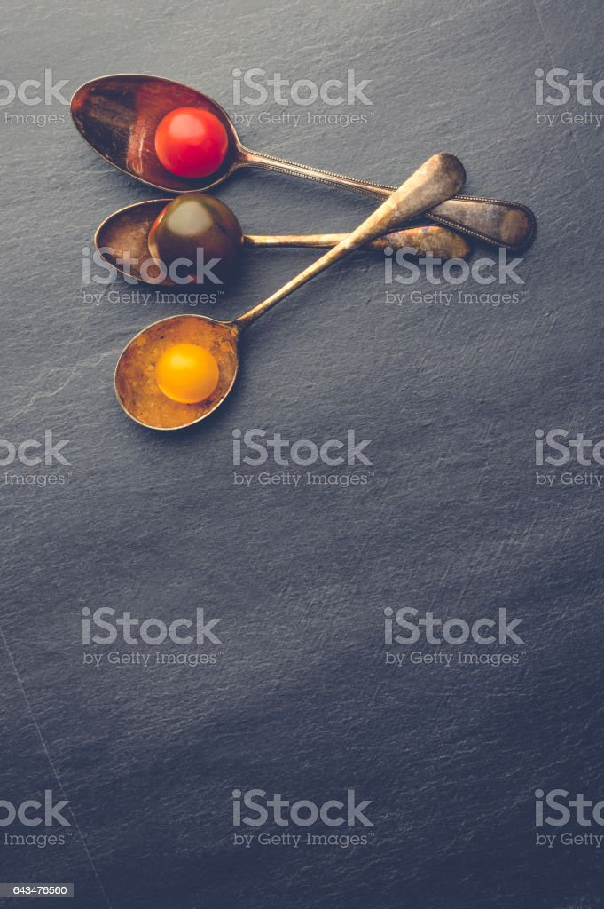 Tomatoes in vintage spoons. stock photo