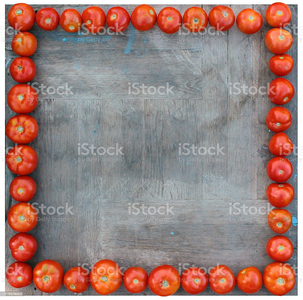 Tomatoes lined up around square wooden board as a frame stock photo