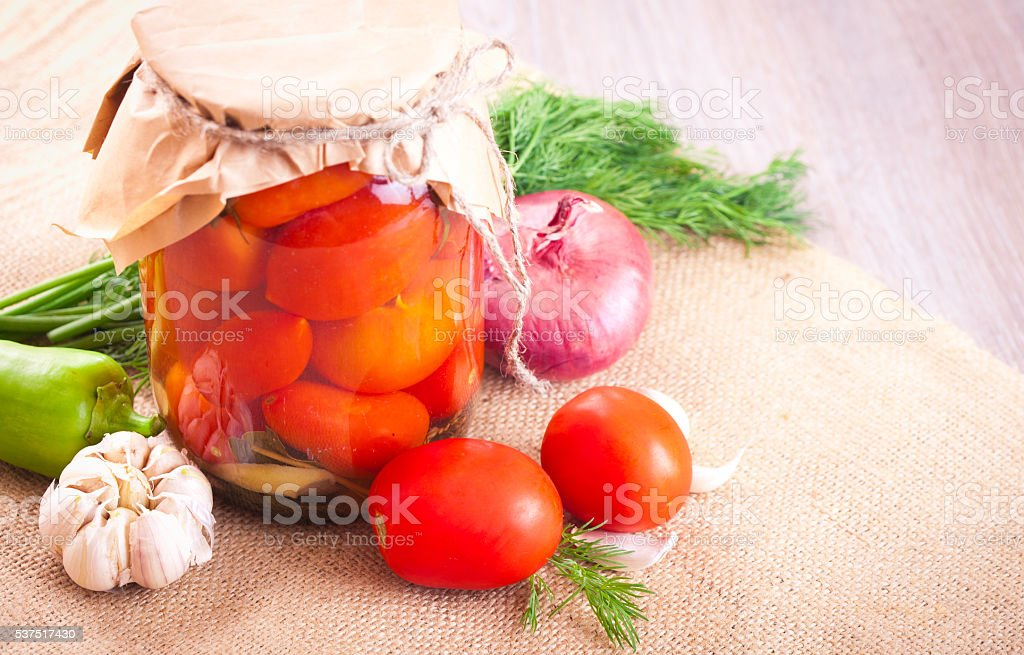 Tomatoes marinated in a jar with spices and vegetables stock photo