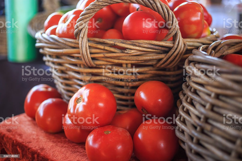 Tomatoes on a table and basket stock photo