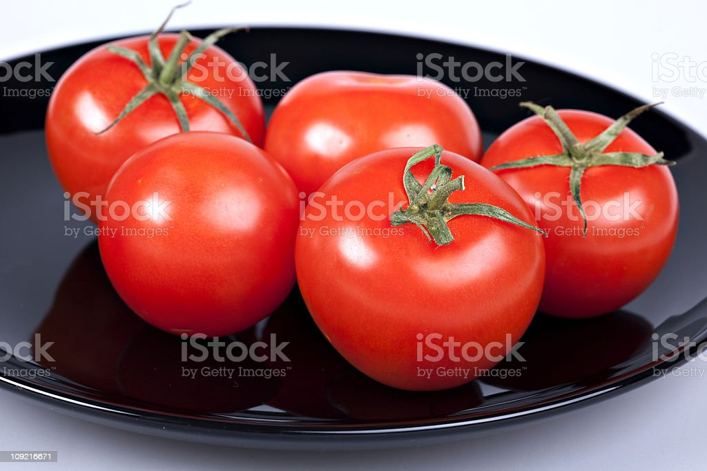 tomatoes on black plate stock photo