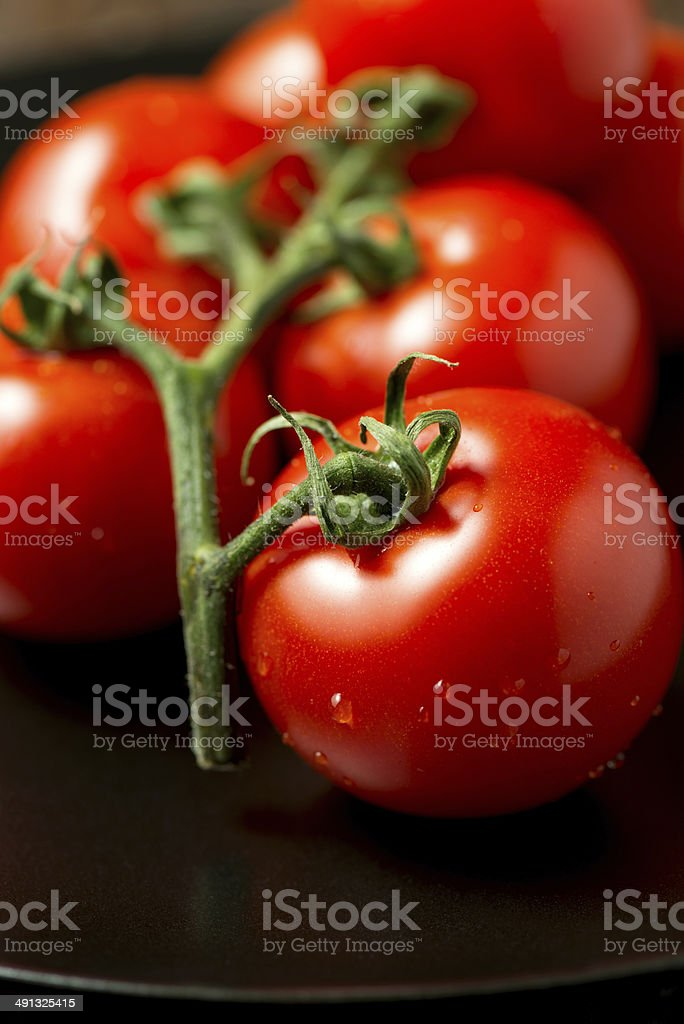 Tomatoes on plate angled view vertical stock photo