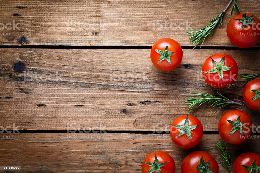 Tomatoes on rustic wood background stock photo