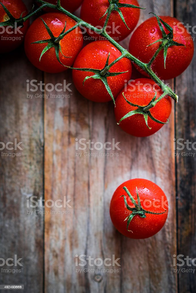 Tomatoes on rustic wooden background stock photo