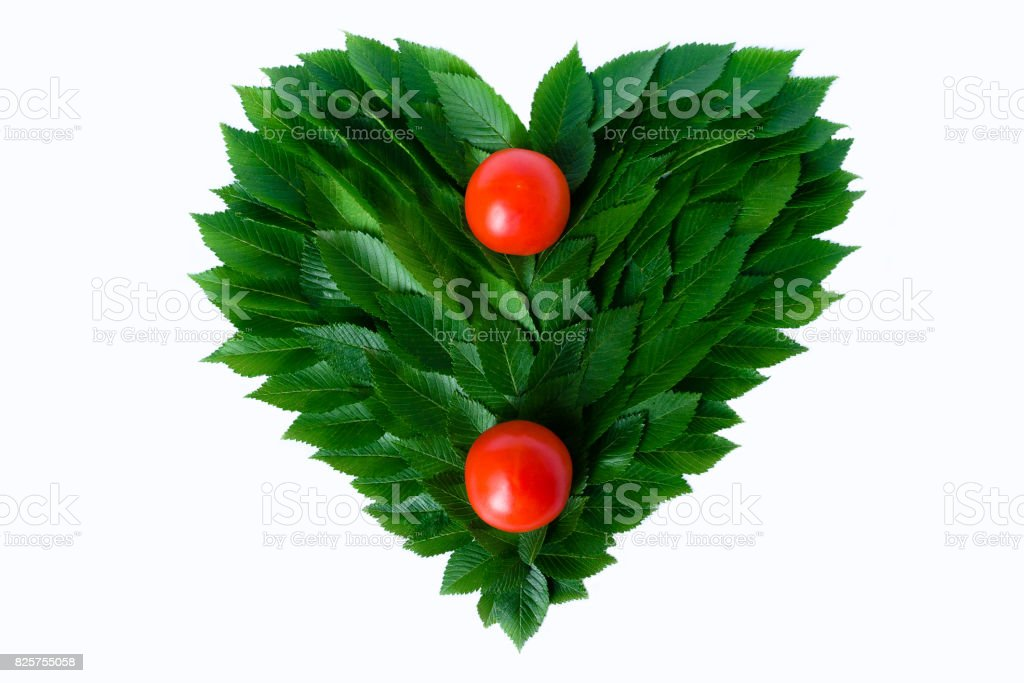 Tomatoes on the background of the heart of green leaves. The concept of love of nature and rational nutrition stock photo
