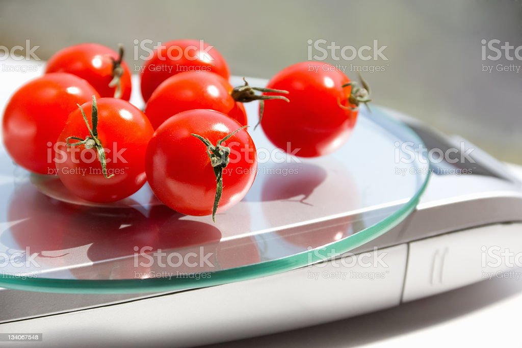 tomatoes on the kitchen scales royalty-free stock photo