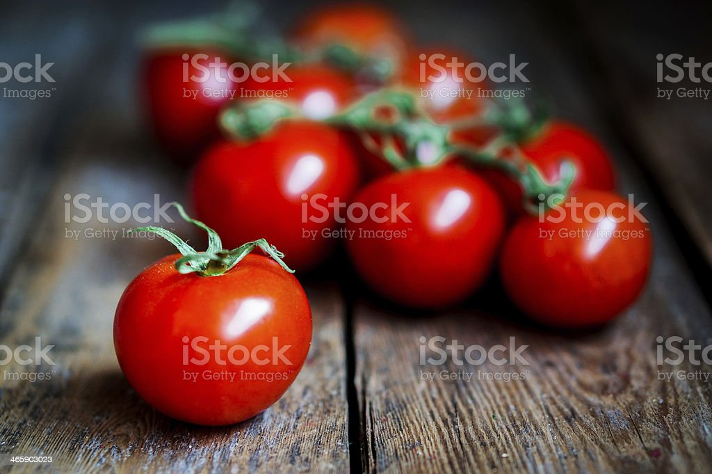 Tomatoes on the vine at rustic wooden background stock photo