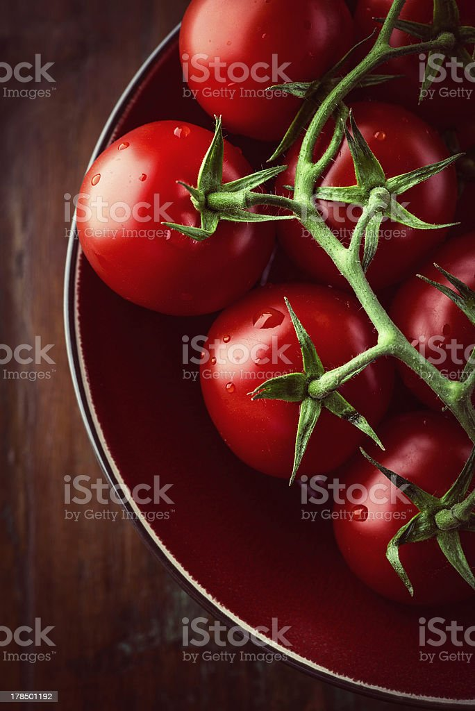 Tomatoes on the vine in a bowl stock photo