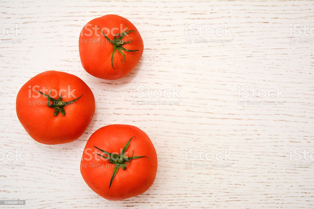 Tomatoes on the white wooden table and copy-space stock photo