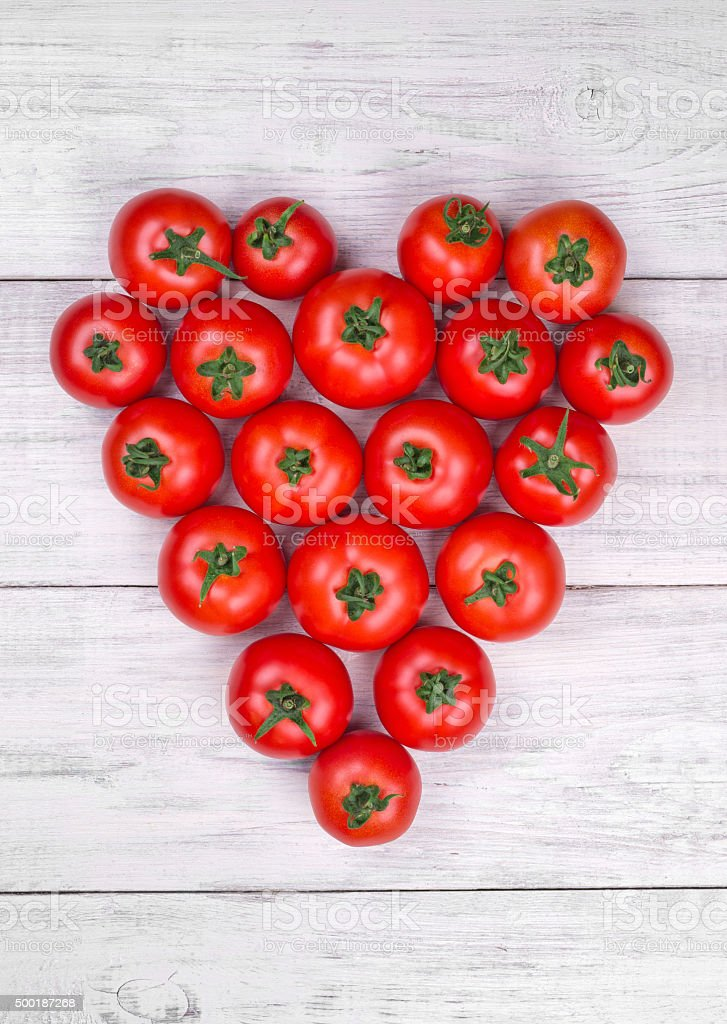 tomatoes on white wooden table, heart top view stock photo