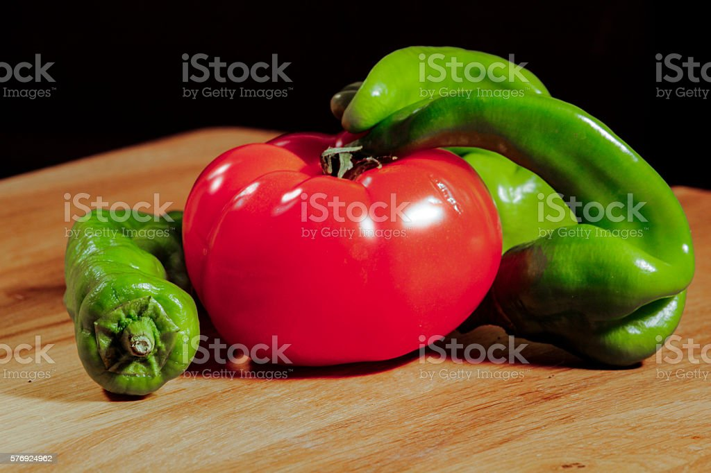 Tomatoes peppers on wooden cutting board stock photo