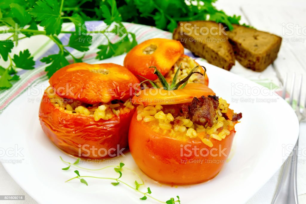 Tomatoes stuffed with bulgur and meat in plate on table stock photo