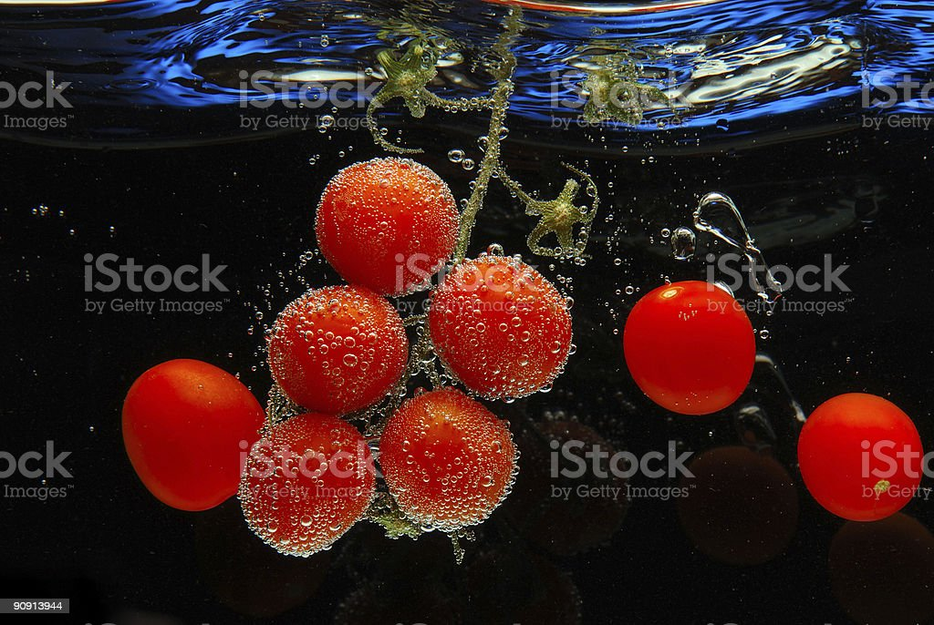Tomatos in the pool of water three on both sides royalty-free stock photo