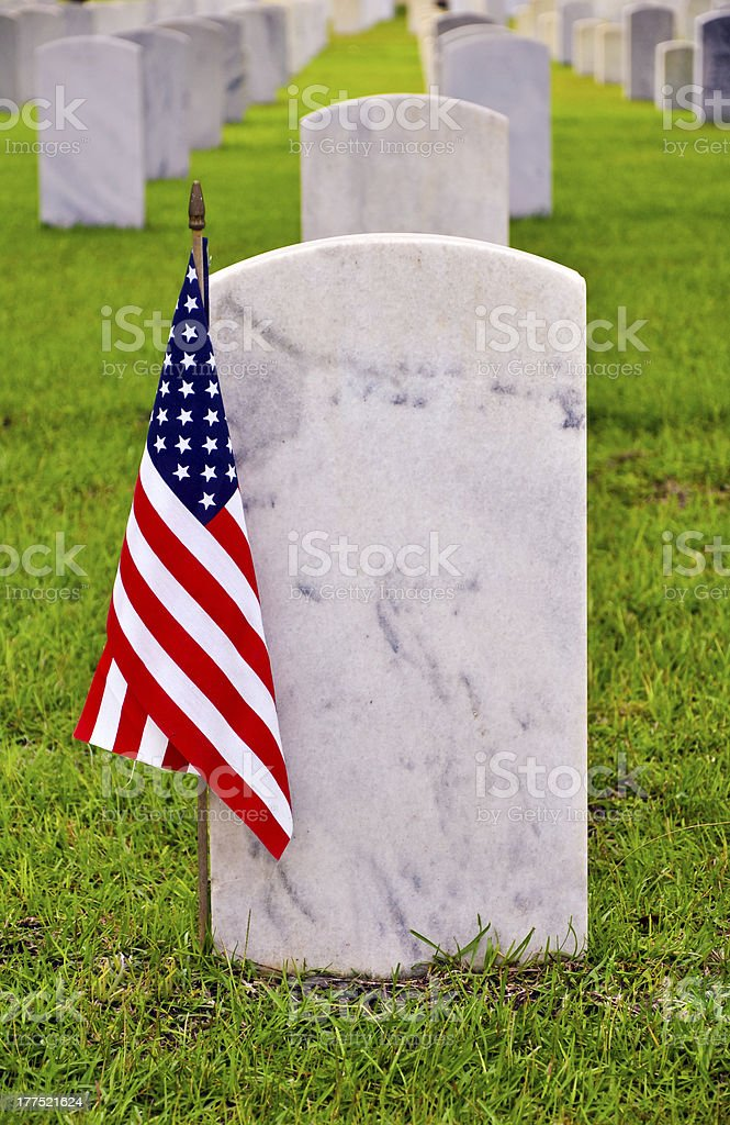 tombstone of a fallen soldier with american flag stock photo