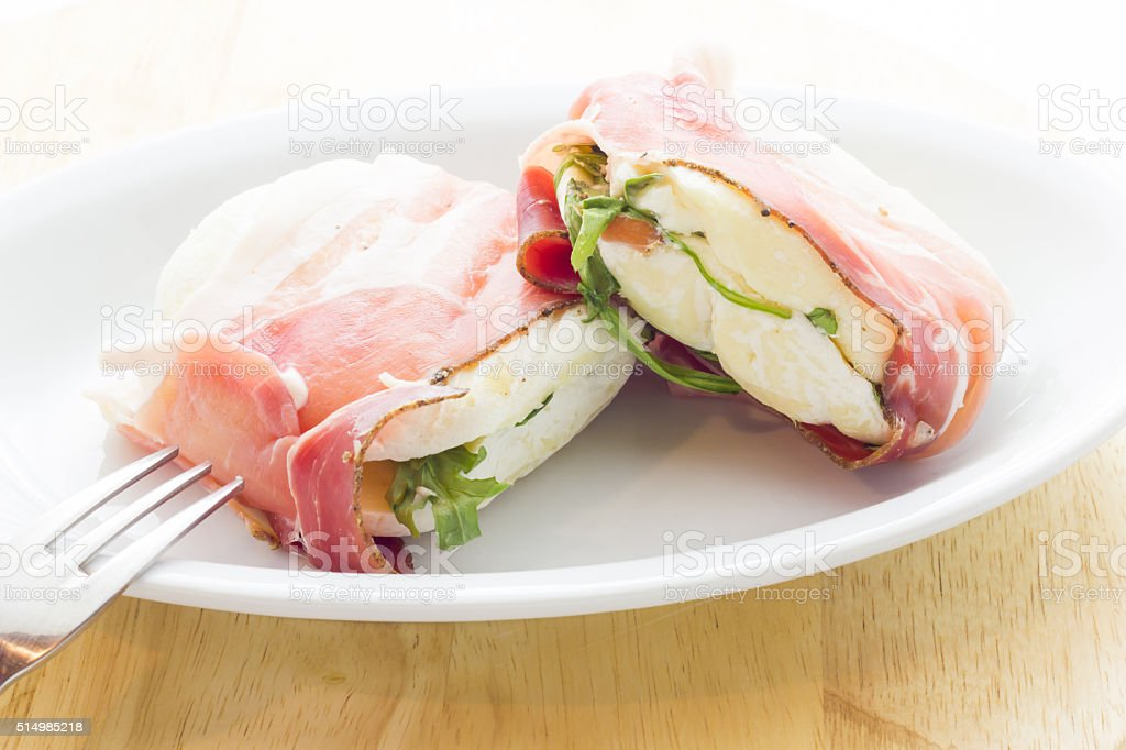 Tomino cheese with bacon stock photo