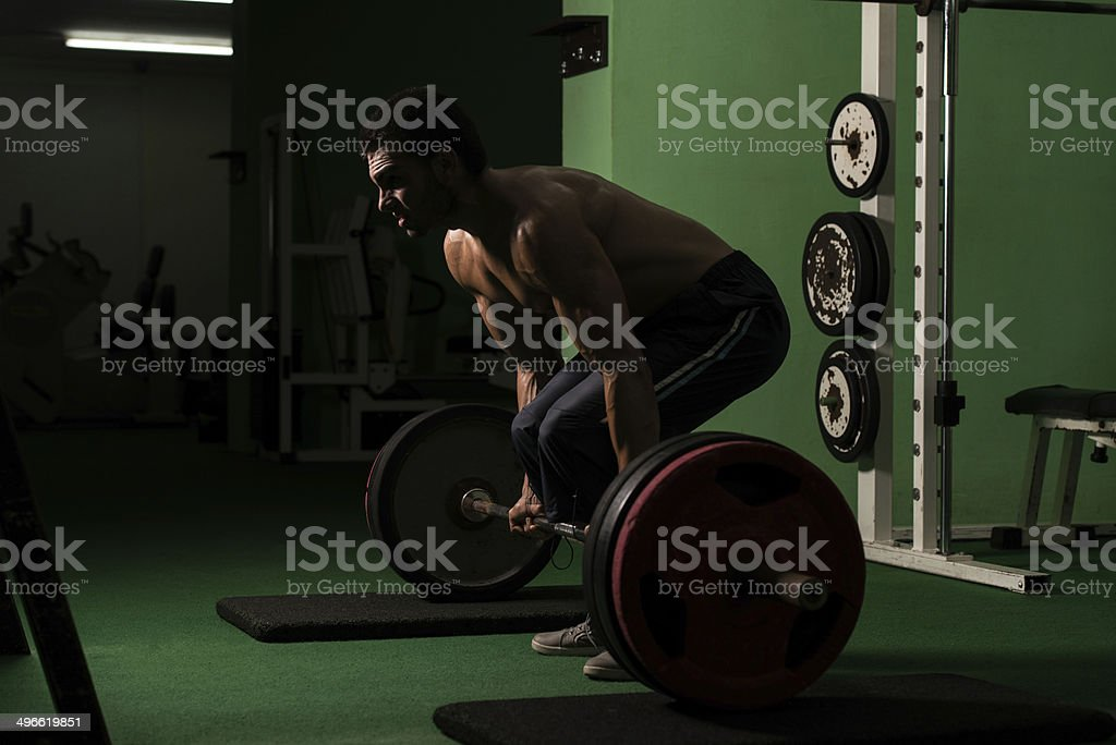 Toned athletic man dead-lifting in a weight room stock photo