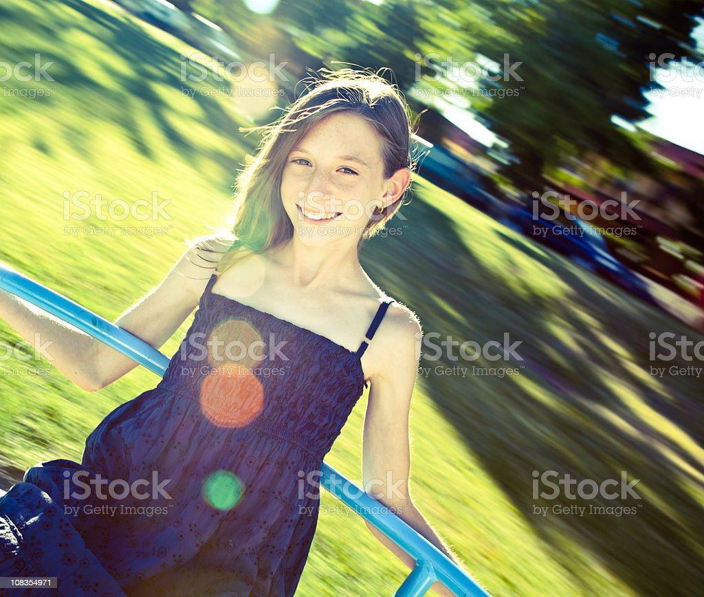 toned beautiful little girls play on carousel at sunny park royalty-free stock photo