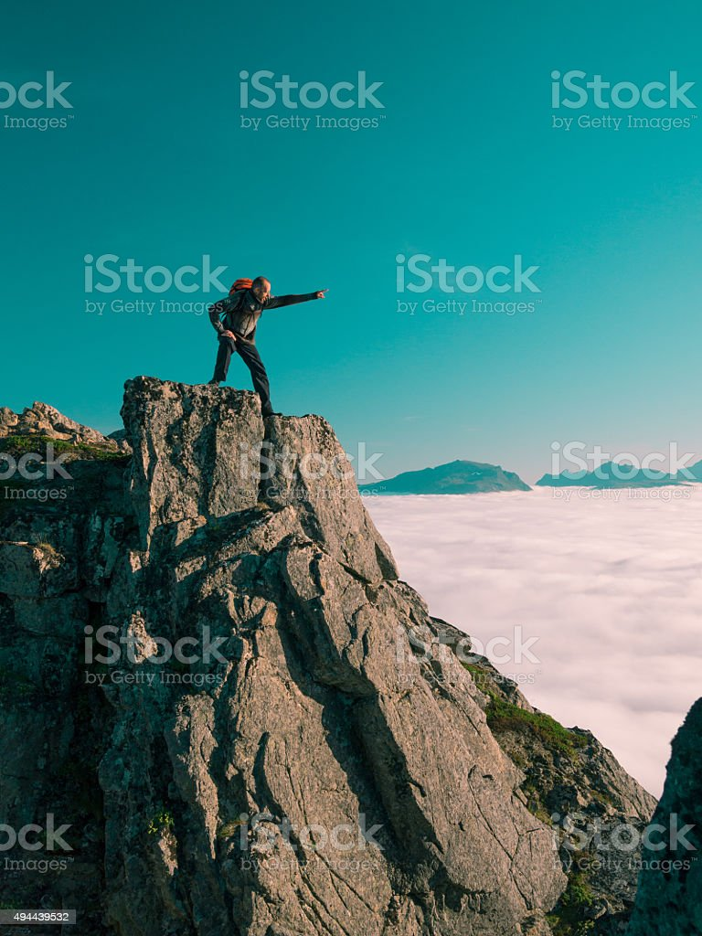 Toned image adult man with backpack stands on edge cliff stock photo