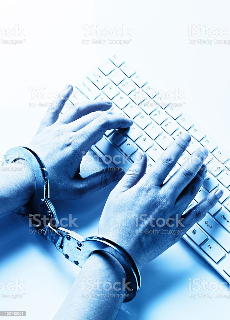 Toned image: looking down on handcuffed hands typing at computer royalty-free stock photo