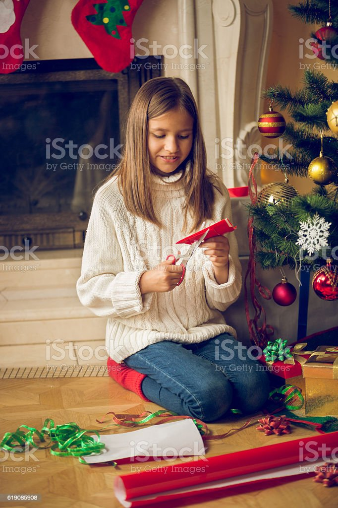 Toned image of girl cutting Christmas ornaments out of paper stock photo