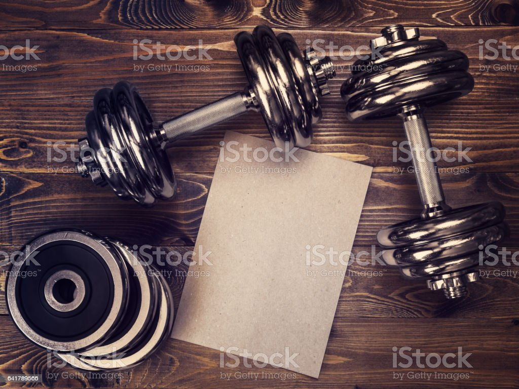 Toned image of metal dumbbells and a sheet of craft paper stock photo