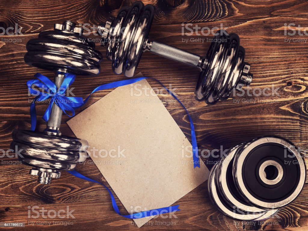 Toned image of metal dumbbells, blue atlas ribbon and a sheet of craft paper stock photo