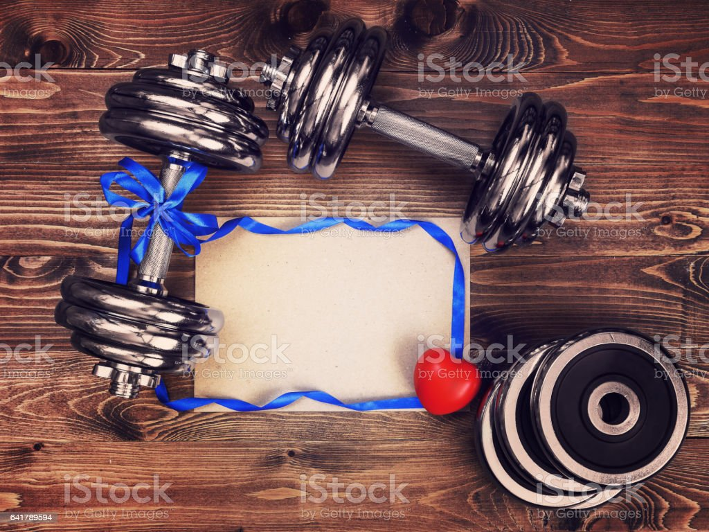 Toned image of metal dumbbells, blue atlas ribbon, red heart and a sheet of craft paper stock photo