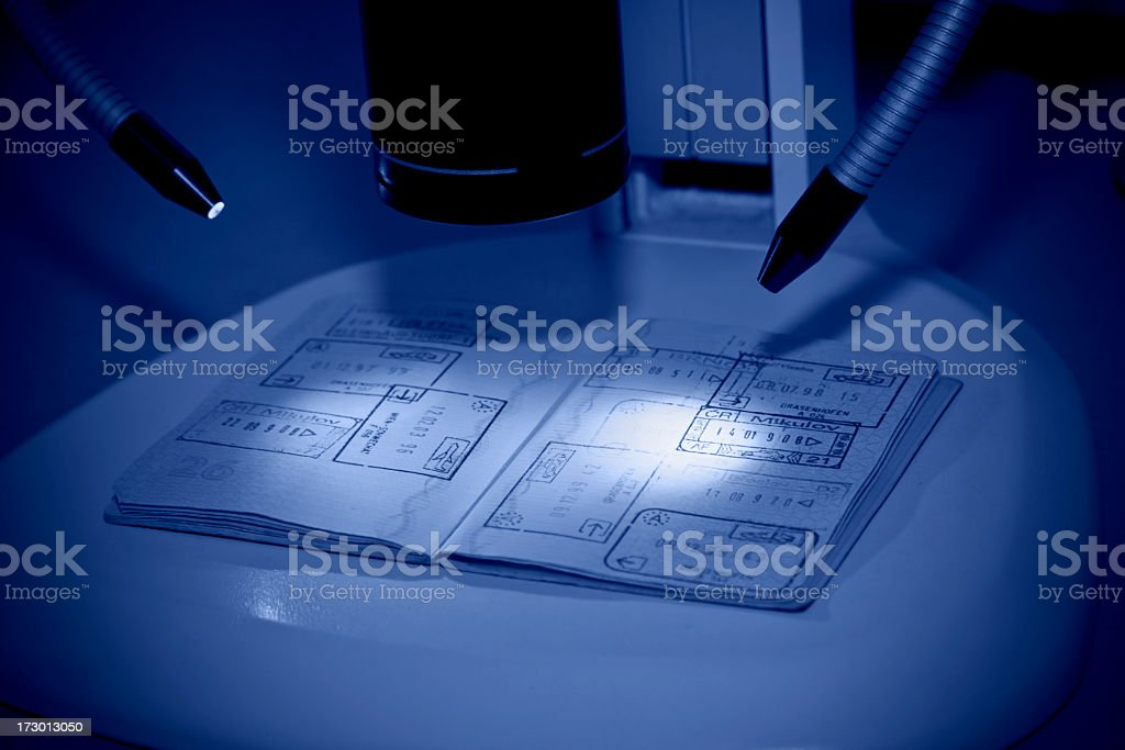 Toned image of passport being examined with a microscope. royalty-free stock photo