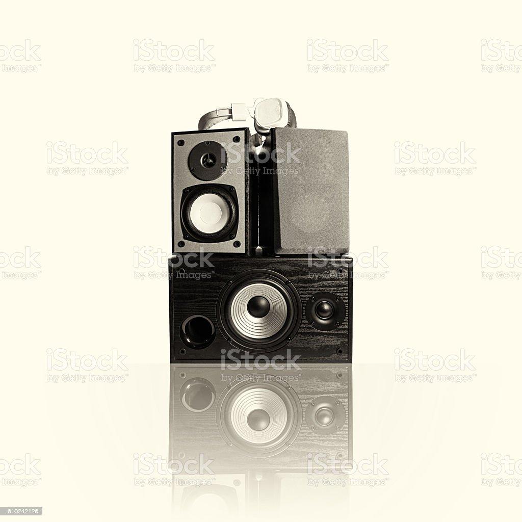 Toned image of three audio speakers and headphones,  isolated stock photo