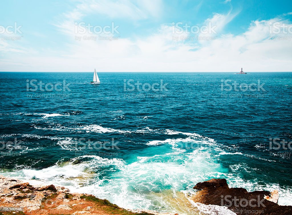 Toned Seascape with Lighthouse and Sailing Yacht stock photo